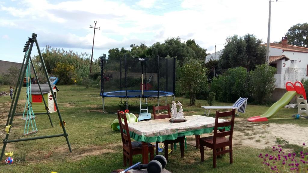 Un grande giardino con tavolo da pranzo e giochi per i piccoli